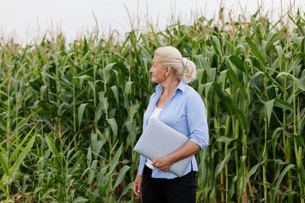 Vrouwelijke landbouwer op het gebied die graaninstallaties controleren tijdens een zonnige de zomerdag