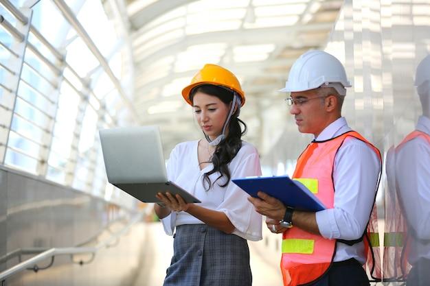 Vrouwelijke laptop van ingenieur with colleague holding tegen bouwwerf