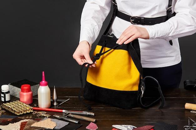 Vrouwelijke leathercrafter aanspanriem van zwart en gele suède tas op de werkplek