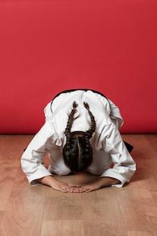 Vrouwelijke leerling begroet haar karate meester