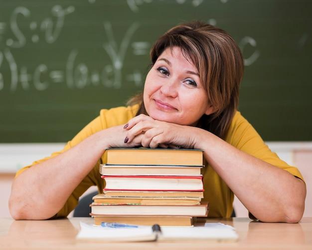 Vrouwelijke leraar aan bureau zittend op stapel boeken