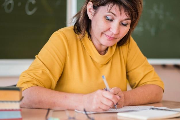 Vrouwelijke leraar aan het bureau dat aantekeningen maakt