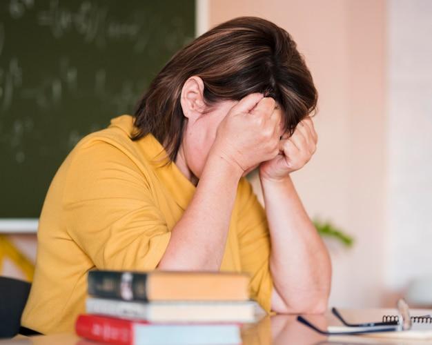 Vrouwelijke leraar aan het bureau moe