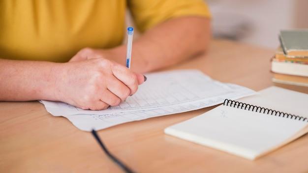 Vrouwelijke leraar bij bureau dat close-up schrijft