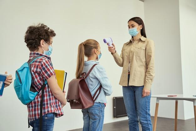 Vrouwelijke leraar die een beschermend masker draagt, screent schoolkinderen op koorts tegen de verspreiding van