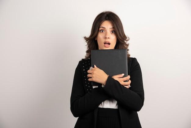Vrouwelijke leraar die een boek met geschokte uitdrukking houdt.