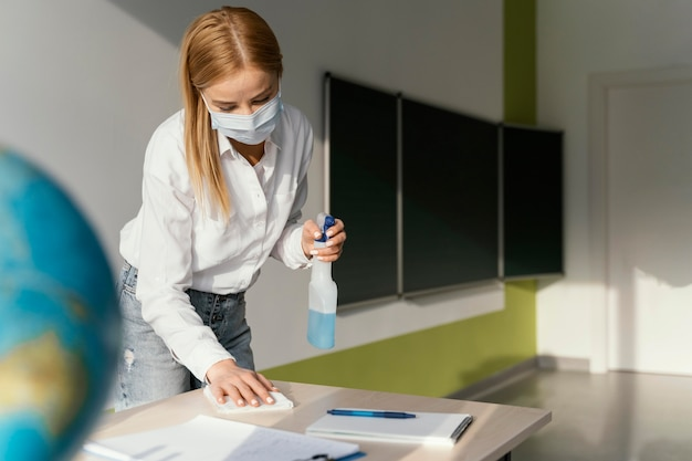 Vrouwelijke leraar die haar bureau in klaslokaal desinfecteert