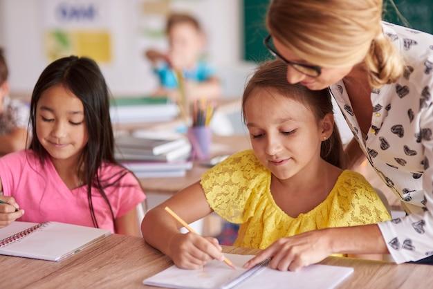 Vrouwelijke leraar die kinderen helpt in oefeningen