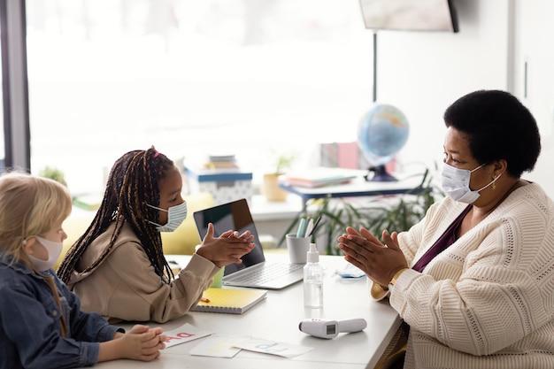 Vrouwelijke leraar die kinderen leert over desinfecteren