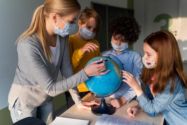Vrouwelijke leraar die met medisch masker aardrijkskunde met aardebol onderwijst in de klas