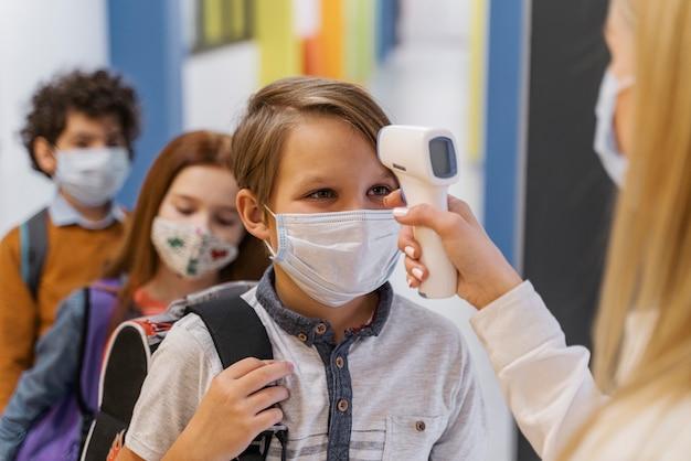 Vrouwelijke leraar die met medisch masker de temperatuur van de student op school controleert