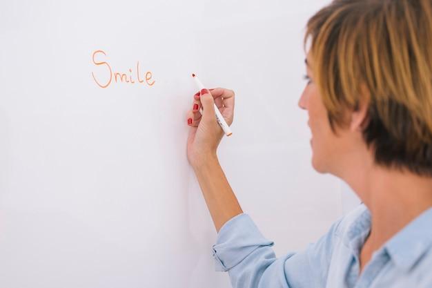 Vrouwelijke leraar die op een whiteboard de woordglimlach schrijft.