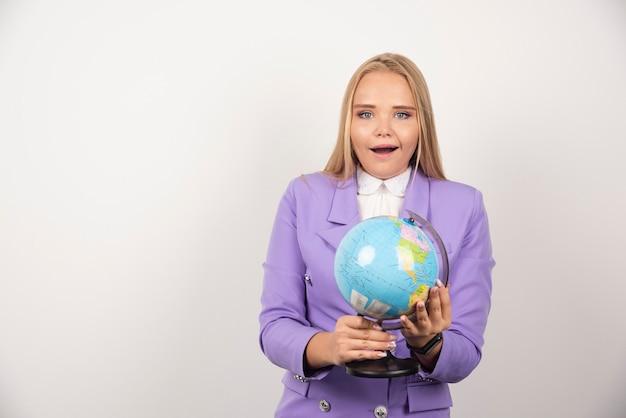 Vrouwelijke leraar die wereldbol met beide handen vasthoudt.