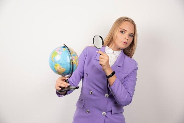 Vrouwelijke leraar die wereldbol met vergrootglas bekijkt.