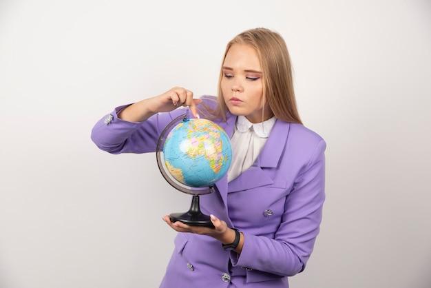 Vrouwelijke leraar die wereldbol op wit bekijkt.