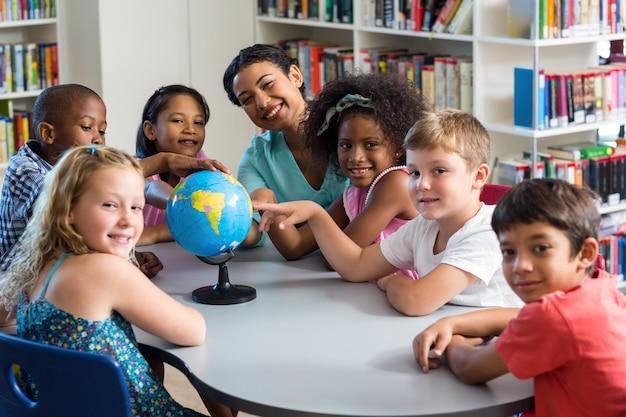 Vrouwelijke leraar en kinderen met globe op tafel
