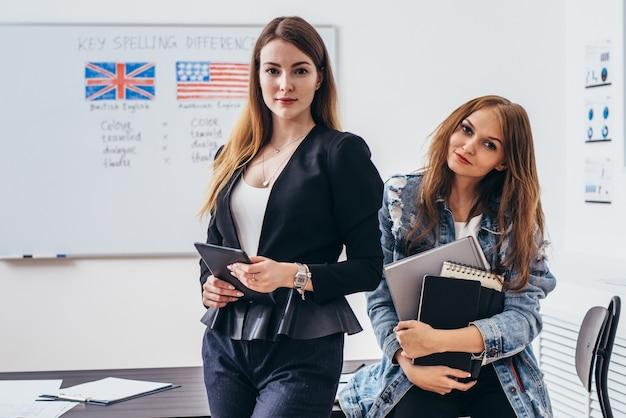 Vrouwelijke leraar en student met boeken in de engelse taalschool van de klas.