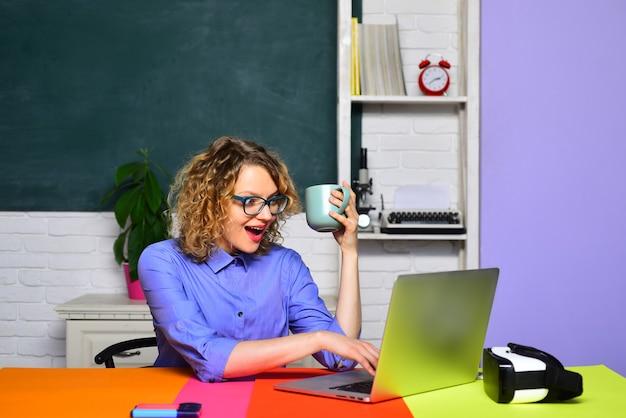 Vrouwelijke leraar in de buurt van schoolbord jonge glimlachende vrouwelijke student die op school studeert, gelukkige student of