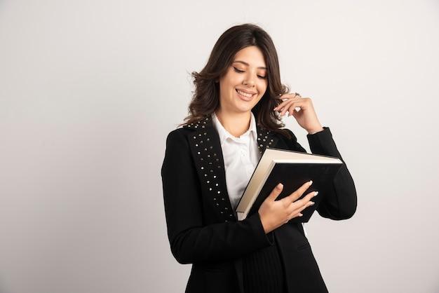 Vrouwelijke leraar leesboek op wit.