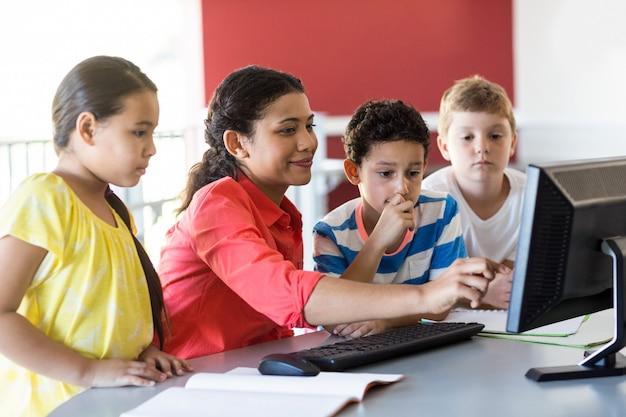 Vrouwelijke leraar lesgeven computer aan kinderen