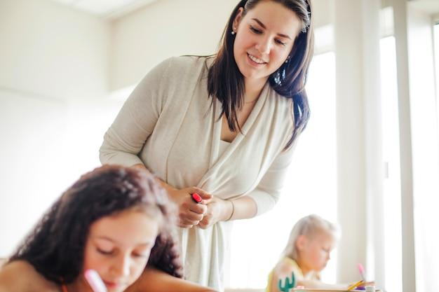 Vrouwelijke leraar leunend over schoolmeisje