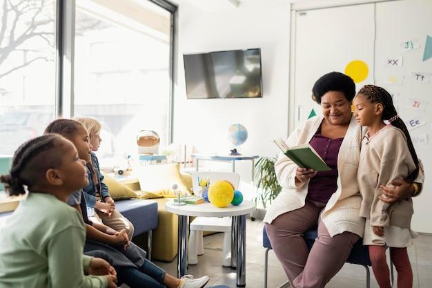 Vrouwelijke leraar lezen voor haar leerlingen