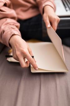 Vrouwelijke leraar met behulp van papier uit de agenda tijdens online les