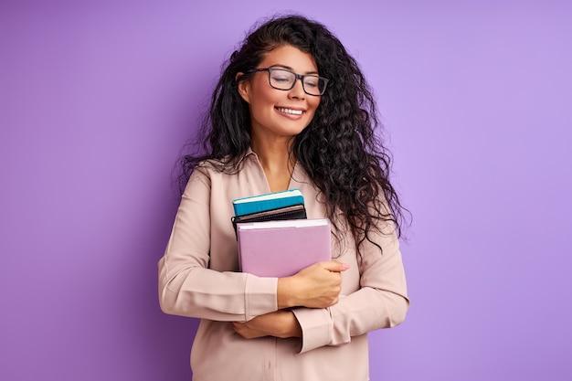Vrouwelijke leraar met boeken in handen geïsoleerd op paarse muur, jonge dame in bril geniet van onderwijs, lach