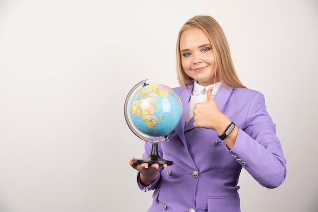 Vrouwelijke leraar met globe maken duimen omhoog op wit.