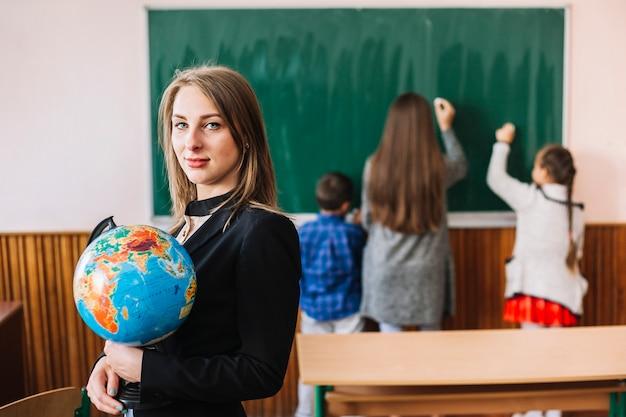 Vrouwelijke leraar met globe op klas achtergrond
