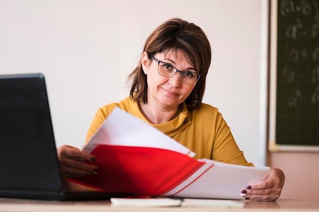 Vrouwelijke leraar met laptop bij bureau