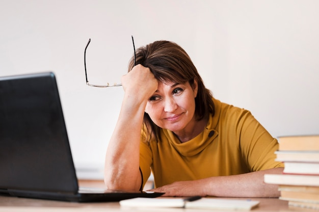 Vrouwelijke leraar met laptop moe