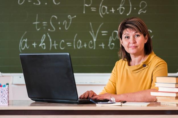 Vrouwelijke leraar met laptop werken