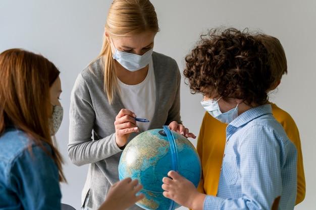 Vrouwelijke leraar met medisch masker die aardrijkskunde met bol in de klas onderwijst