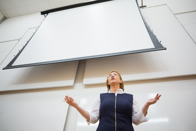 Vrouwelijke leraar met projectiescherm in de collegezaal