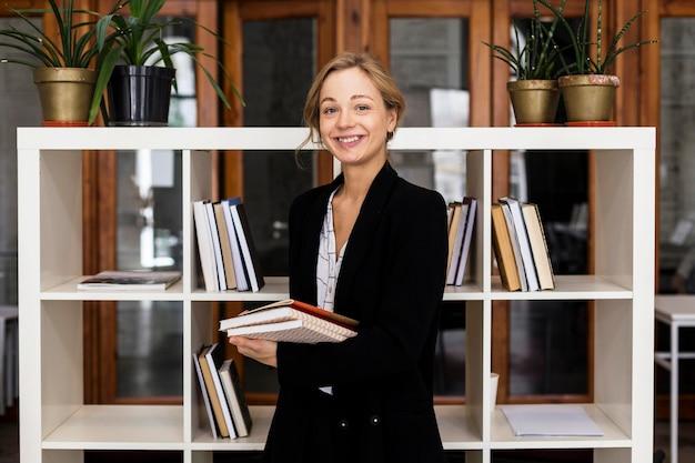 Vrouwelijke leraar met stapel boeken