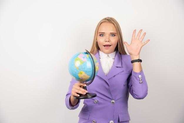 Vrouwelijke leraar poseren met globe op wit.