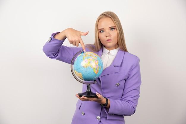 Vrouwelijke leraar wijzend op wereldbol op wit.