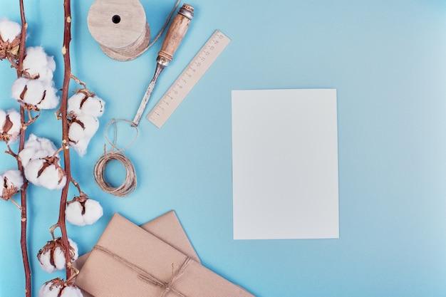 Vrouwelijke lichtblauwe achtergrond met tak van katoen bloem. katoen, geschenkdozen, jute touwklos en blanco papier. plat leggen, kopie ruimte.