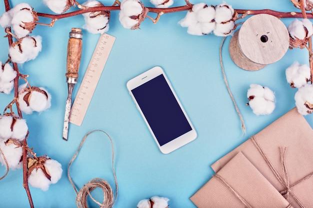 Vrouwelijke lichtblauwe achtergrond met tak van katoen bloem. katoen, geschenkdozen, smartphone en jute touw.