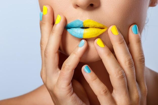 Vrouwelijke lippen met twee verschillende lippenstiften en kleurrijke nagels