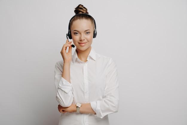Vrouwelijke live technische ondersteuningsmedewerker in wit overhemd met headset die persoon vertelt hoe programmafout kan worden opgelost, zelfverzekerd en zeker van oplossing, poserend op grijze islolated achtergrond. callcenterconcept