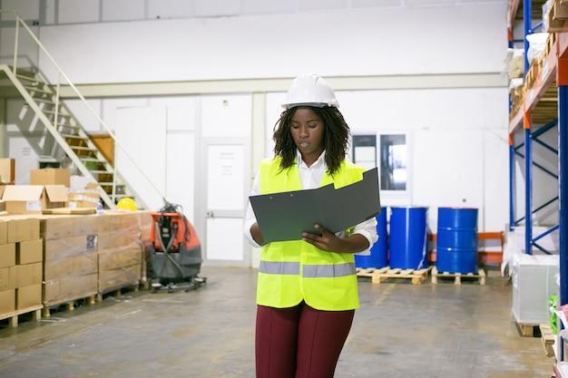 Vrouwelijke logistieke werknemer gericht in veiligheidshelm en veiligheidsvest wandelen in magazijn, uitvoering open map, document kijken. kopieer ruimte, vooraanzicht. arbeids- en inspectieconcept