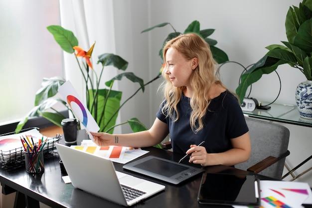 Vrouwelijke logo-ontwerper werkt aan haar tablet die is aangesloten op een laptop