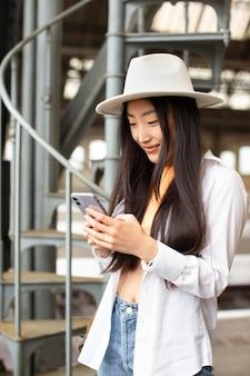 Vrouwelijke lokale reiziger die haar telefoon controleert