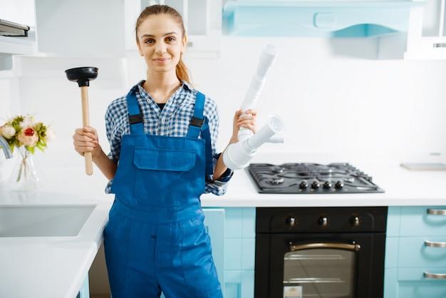 Vrouwelijke loodgieter in uniform houdt zuiger en pijp