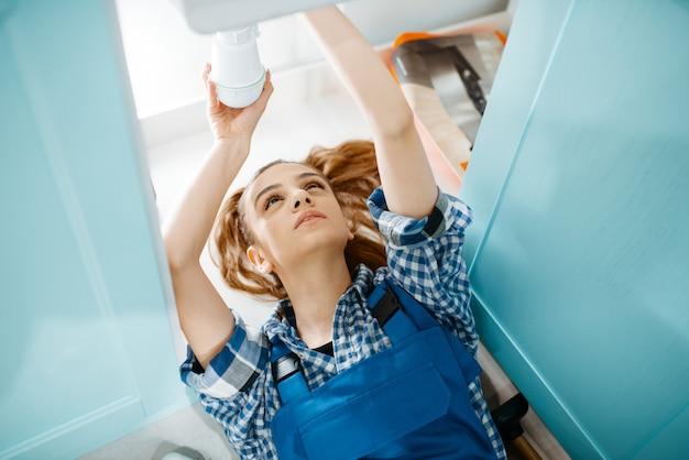 Vrouwelijke loodgieter liggend op de vloer, bovenaanzicht