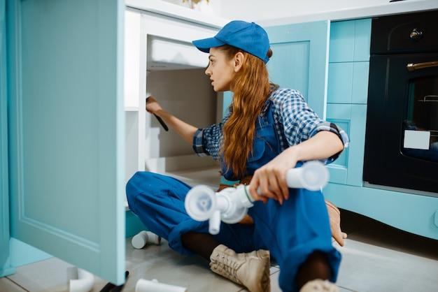 Vrouwelijke loodgieter tot vaststelling van probleem met afvoerpijp