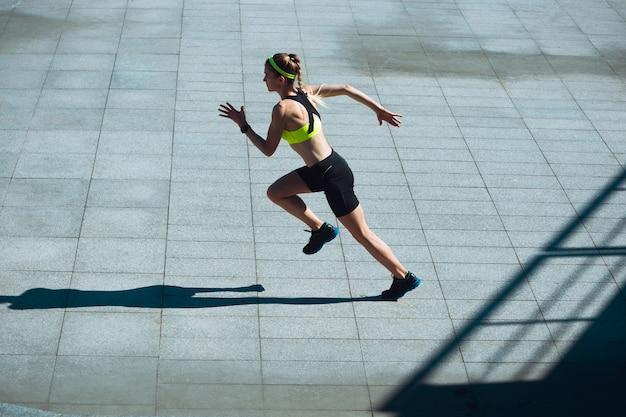 Vrouwelijke loper, atleet training buitenshuis. professionele hardloper, jogger die op straat traint.