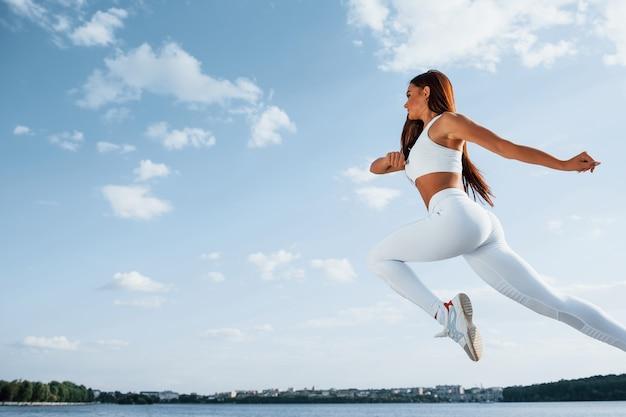 Vrouwelijke loper in witte sportieve kleding die fitness doet
